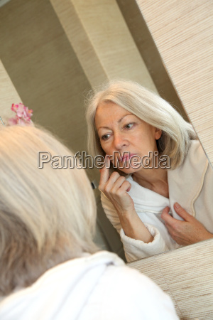 senior woman applying moisturizer on her