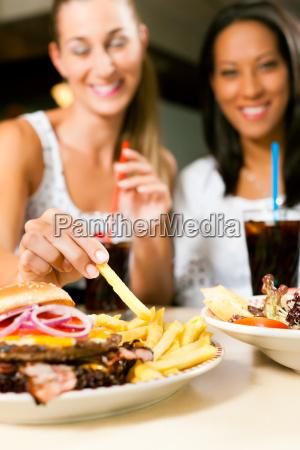 dos mujeres que comen la hamburguesa