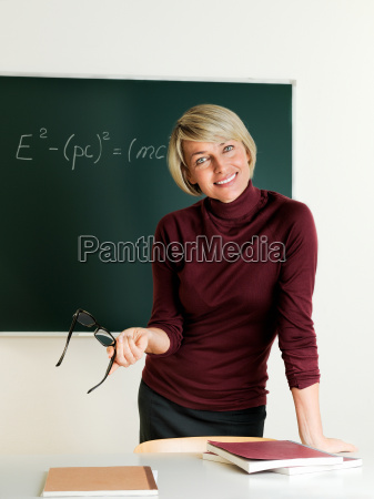 teacher standing at blackboard and teaches