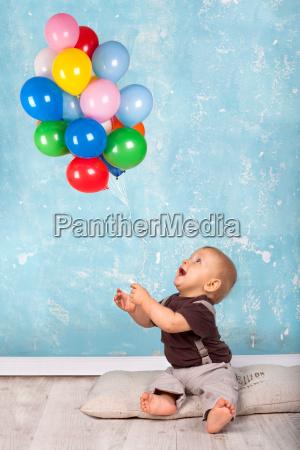 rapaz pequeno que joga com baloes